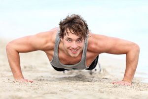 fitness man exercising push ups smiling happy. Male fitness model cross-training on beach. Caucasian man in his twenties.