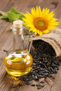 sunflower oil, seed and sunflower on the background of wooden boards