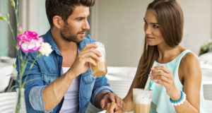 Young-couple-talking-and-drinking-coffee