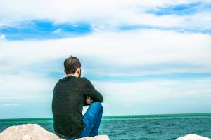 solitary man looking out in the ocean horizon