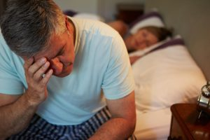man with insomnia sitting on edge of bed while wife sleeps