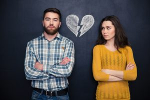 divorced couple, arms crossed, broken heart on wall