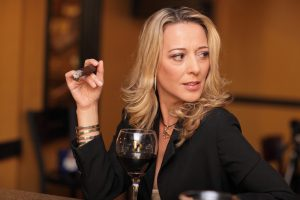 mature confident woman smoking tobacco and drinking wine