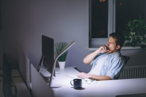man yawning working late at night is looking up Progentra online