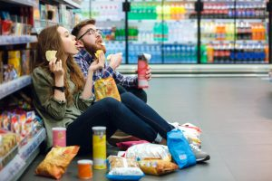 couple eating junk food at a store after picking up some Progentra pills