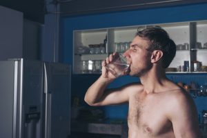 man drinking water in the middle of night to take his Progentra pill