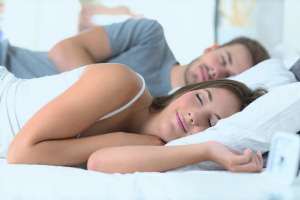 happy couple in bed while sleeping