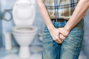 man holding off his pee